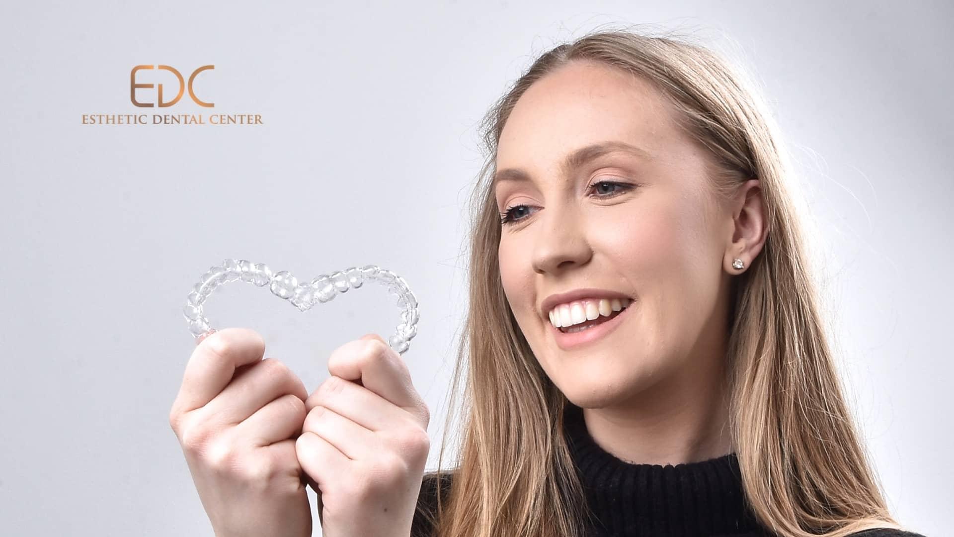 Mlada pacijentica drži Invisalign, prozirni aparatić za zube