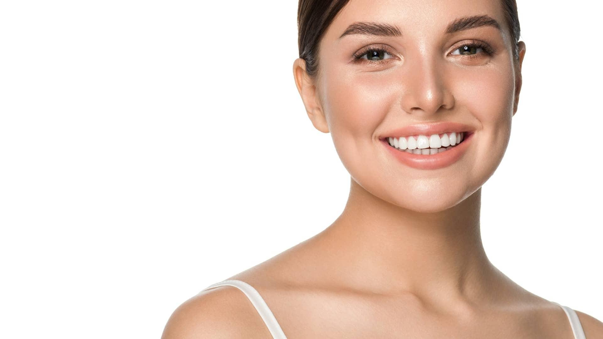 Mlada žena s bijelim zubima nakon izbjeljivanja